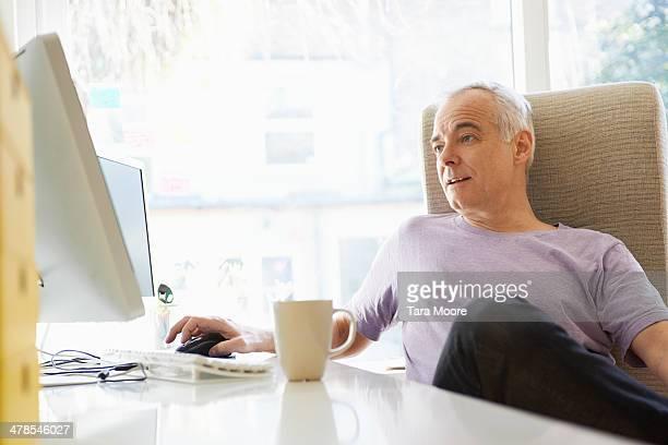 mature man looking at home computer