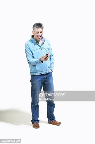 Mature man looking at mobile phone, smiling