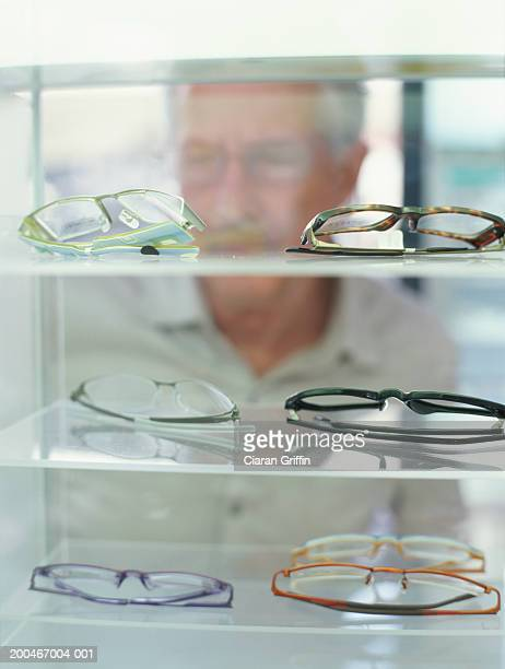 Mature man looking at spectacles
