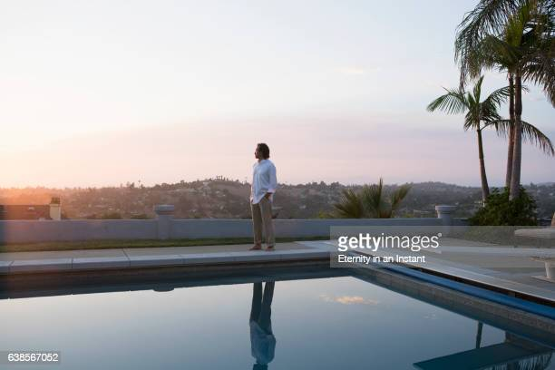 Mature man looking at the sunset by his swimming pool
