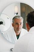 Mature Man Looking in Mirror