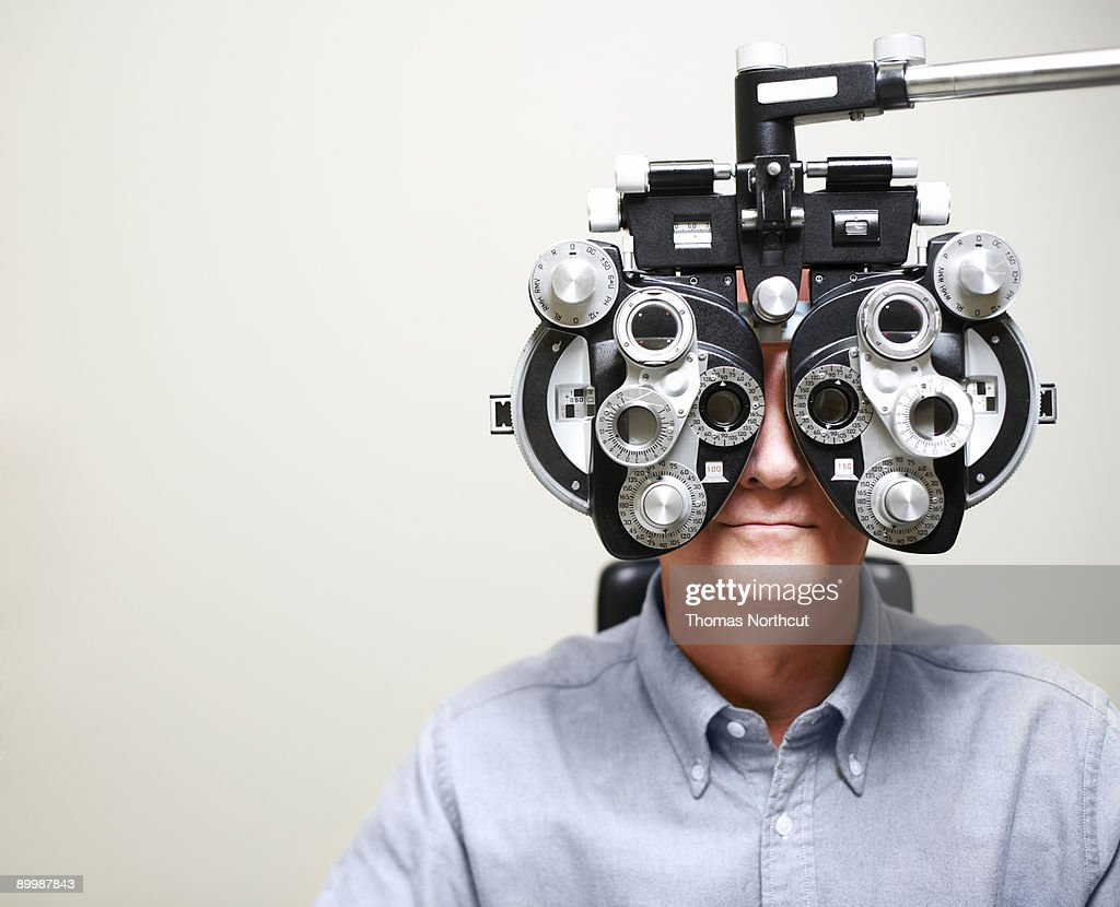 Mature Man looking through Phoroptor : Stock Photo