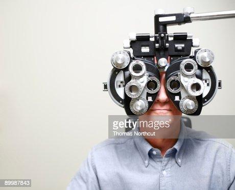 Mature Man looking through Phoroptor : Stock Photo
