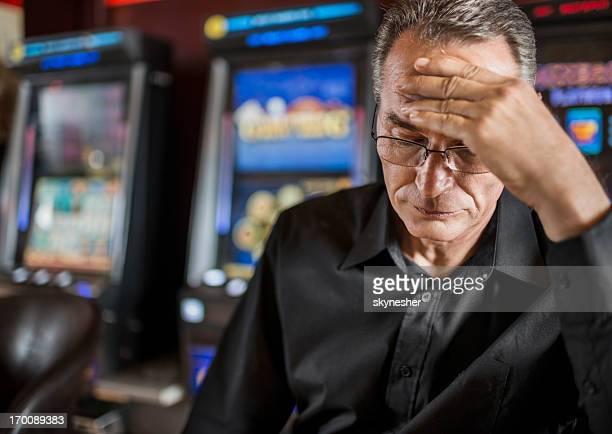 Uomo maturo compromettere il suo denaro su slot machine.