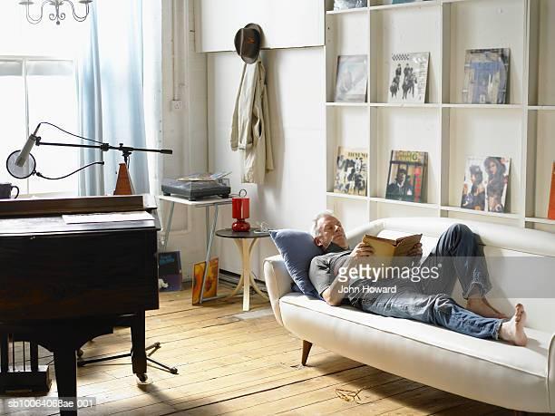 Mature man lying down, reading