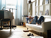 Mature man lying on couch listening to music