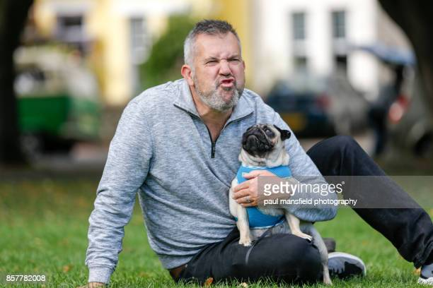Mature man making a funny face whilst sitting with his pet dog