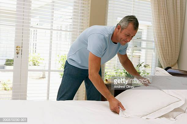 Mature man making bed, smiling