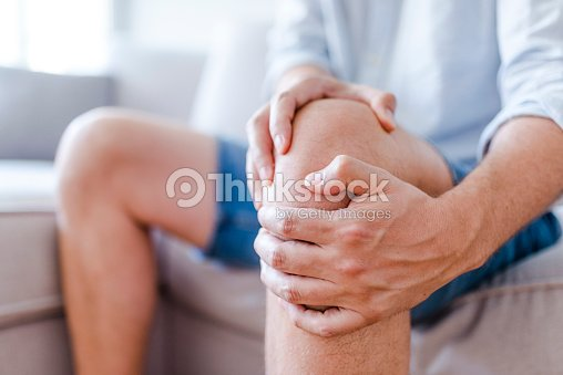 A mature man massaging his painful knee : Stock Photo