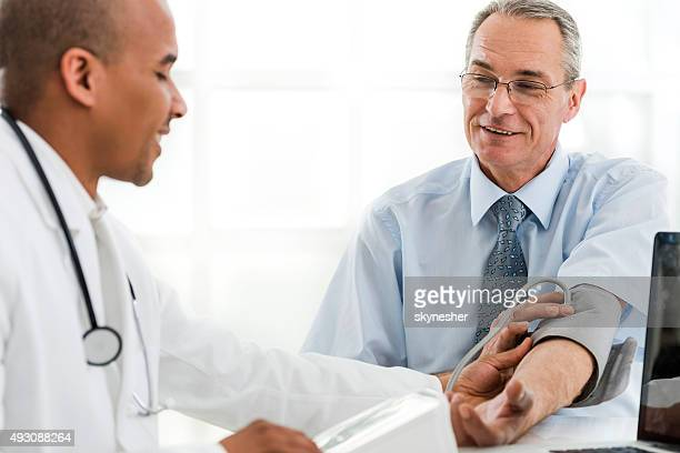 Mature man measuring blood pressure at doctor's office.
