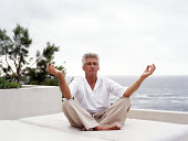 Mature man meditating by ocean, eyes closed