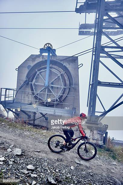 Mature man mountain biking past cable car, Valais, Switzerland