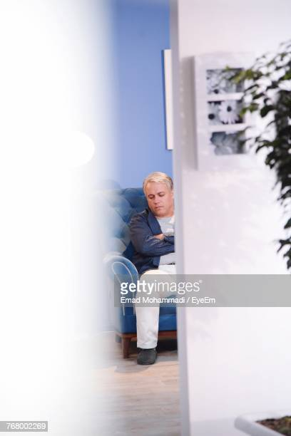 Mature Man Napping While Sitting On Chair Seen Through Door