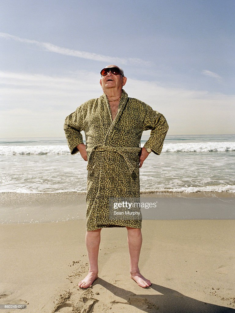 Mature man on beach wearing sun glasses and leopard print robe