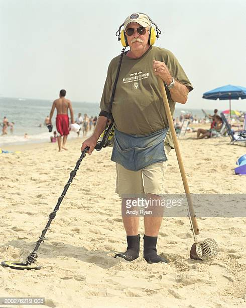 Mature man on beach with metal detector, portrait