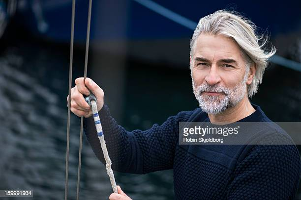Mature man on boat holding rope