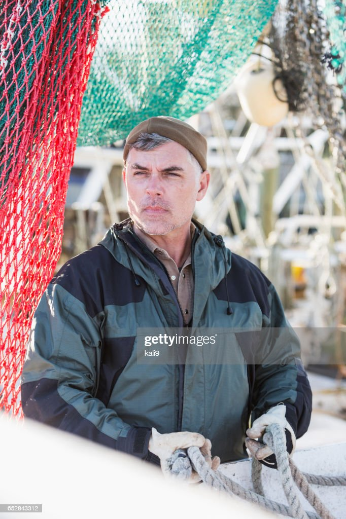 Mature man on commercial fishing boat surrounded by nets : Stock Photo