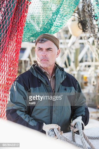 Mature man on commercial fishing boat surrounded by nets : Stockfoto