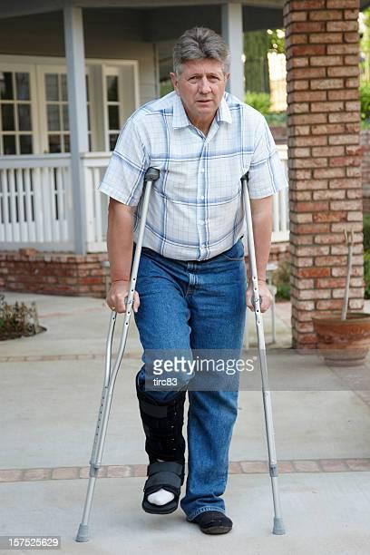 Homme d'âge mûr sur béquilles