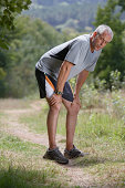 Mature man on dirt track, hands on knees, catching breath