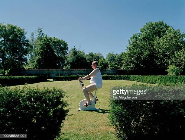 Mature man on exercise bike in garden, side view