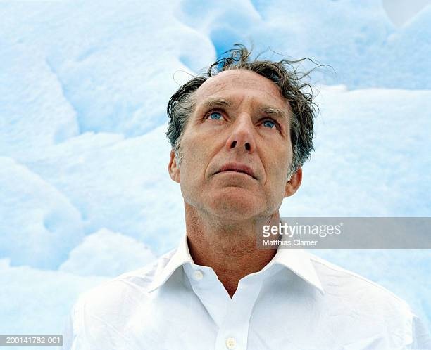 Mature man on glacier looking upward, close up