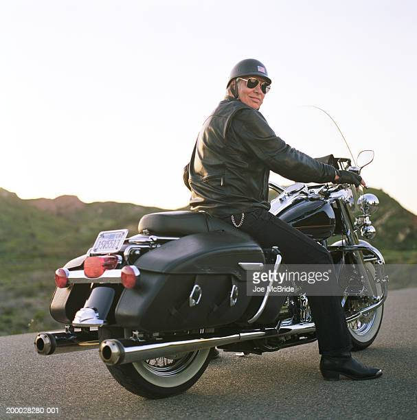 Mature man on motorcycle, wearing leather jacket, portrait, rear view