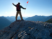 Mature man on mountain summit holding flag, arms outstretched, rear view, mountain range in background