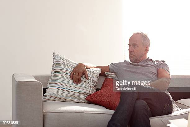 Mature man on sofa looking away seriously