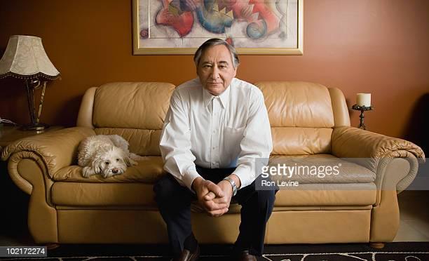 Mature man on sofa with his pet dog