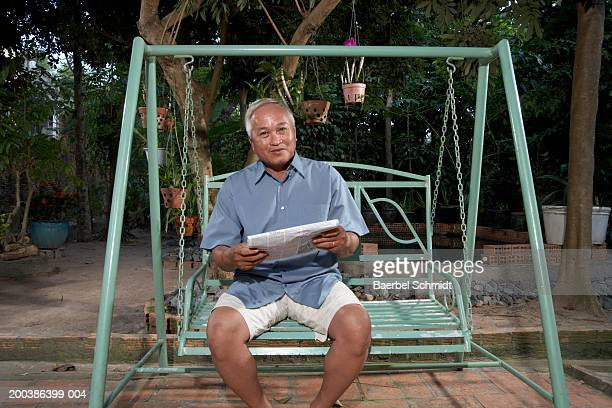 Mature man on swing with newspaper smiling, portrait