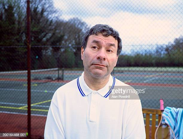 Mature man on tennis court, looking to side