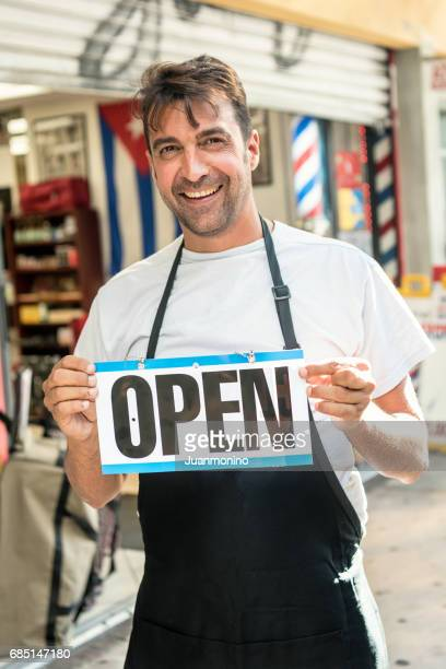 Mature man outside his business holding an open sign