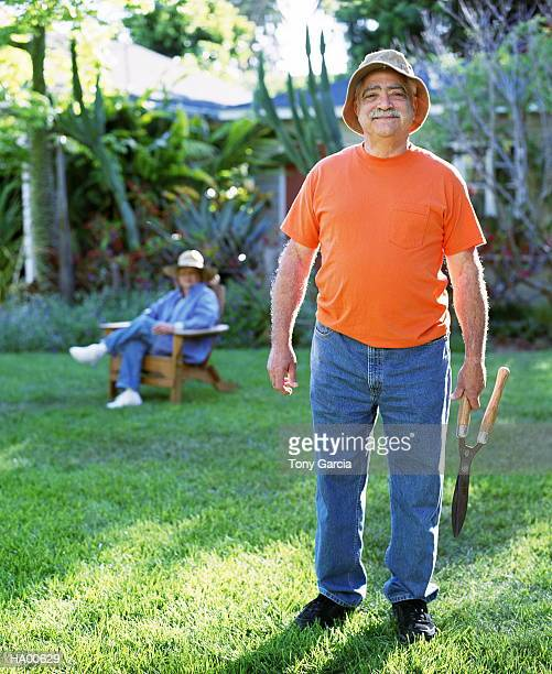 Mature man outside holding plant clippers, wife in background