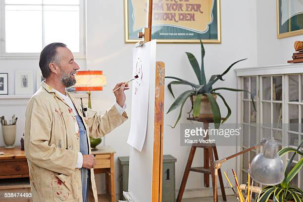 Mature man painting at his home studio