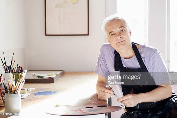 mature man painting in studio