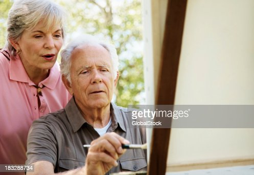 Mature man painting on canvas with his wife