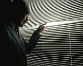 Mature man peeking through window blinds
