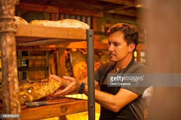 Mature man placing fresh bread on shelf