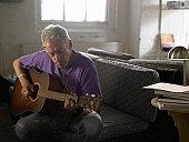 Mature man playing acoustic guitar