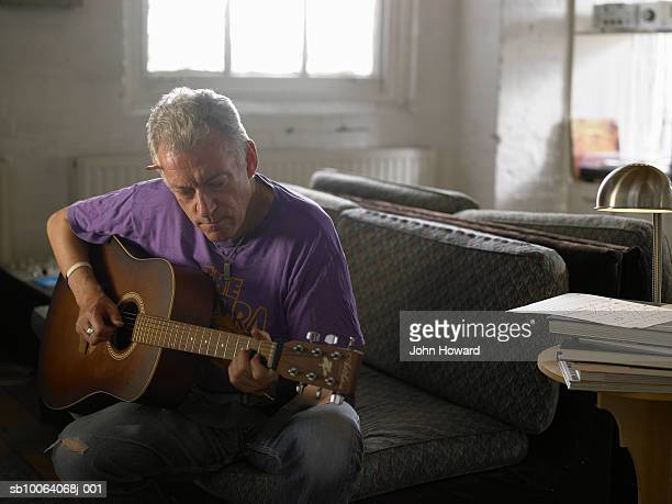 Mature man playing acoustic guitar
