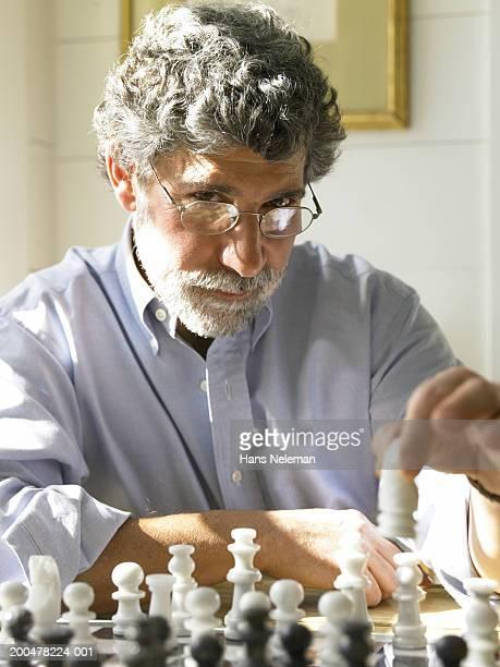 Mature man playing chess, portrait