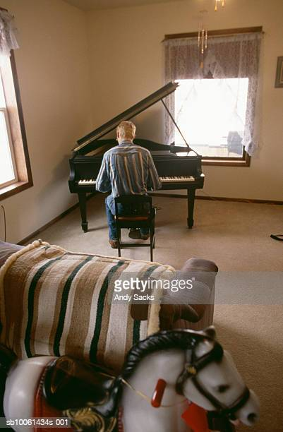 Mature man playing piano, rear view