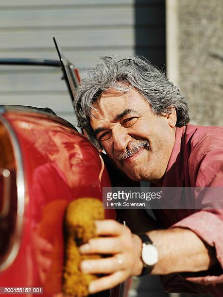 Mature man polishing side of classic sports car, close-up