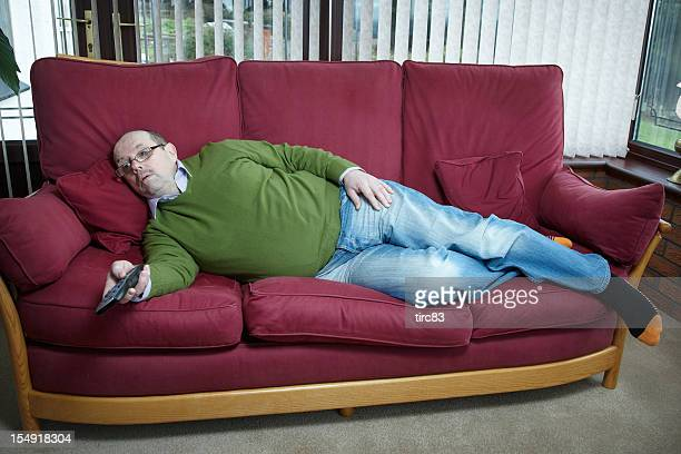 Mature man portrait lying on sofa with TV remote
