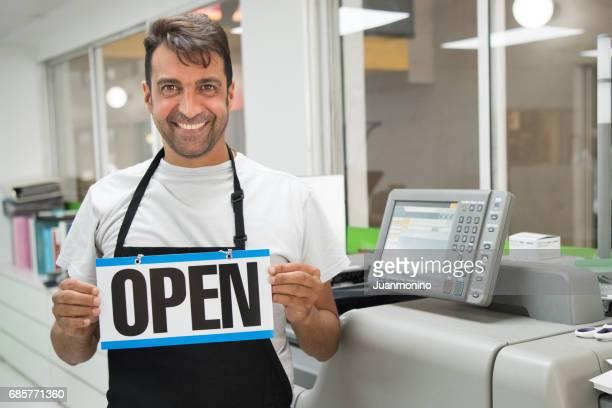 Mature man posing at his printing-graphic design shop
