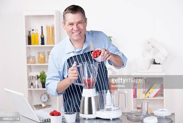 Uomo maturo versare lamponi e fare frullati nel frullatore/Dessert