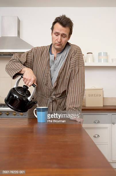 Mature man pouring water from kettle into mug in kitchen