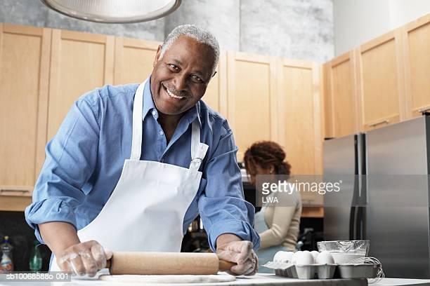 Mature man preparing food in kitchen, smiling