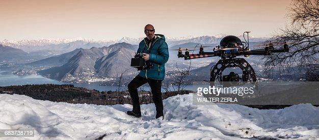Mature man preparing to fly drone, Stresa, Piedmont, Italy
